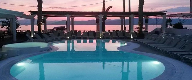 Evening view of Kavos hotel swimming pool overlooking mediterranean sea