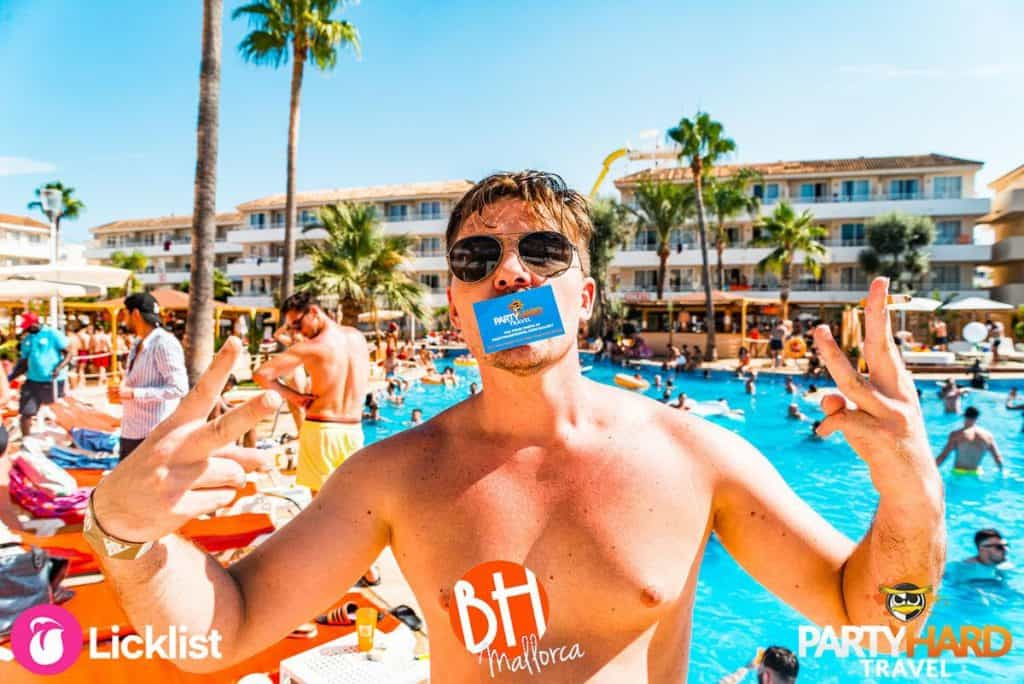 Lad Posing with Party Hard Travel Entry Card on His Face in Front of Busy Pool