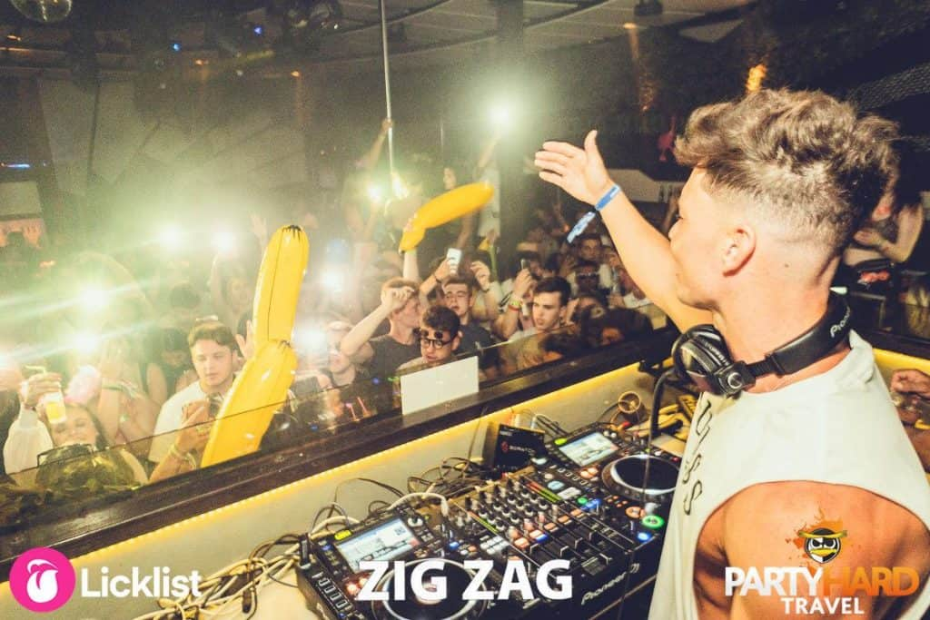 Joel Corry top professional DJ addresses the clubbers waving yellow inflatables
