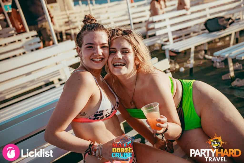 Two Girl Friends on Deck of the Malia Booze Cruise Enjoying a Quiet Drink