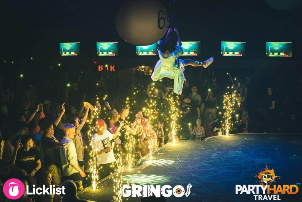 Performer swinging across the stage as fireworks ignite at Gringos Club Magaluf