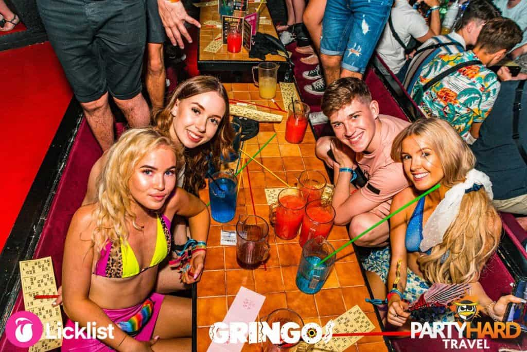 Three girls with lad at Gringos Club posing for photo with their fruit cocktails and Bingo cards