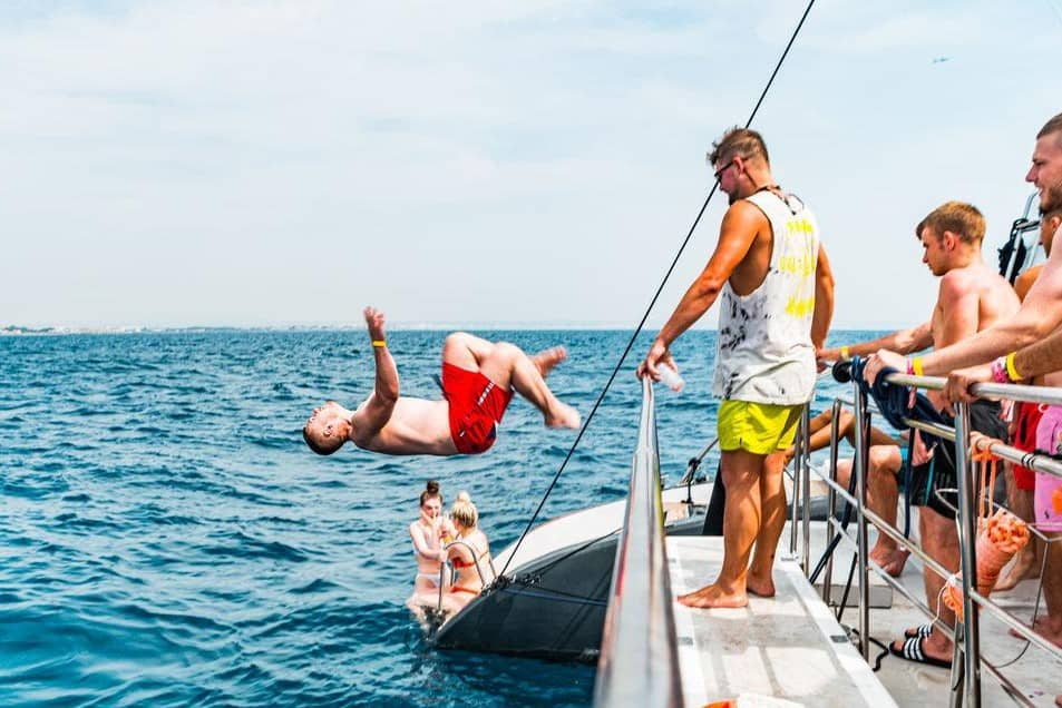 boy jumping off magaluf booze cruise
