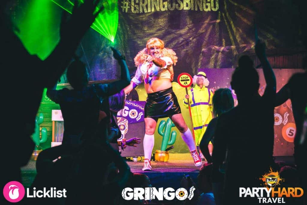 Man dressed as schoolgirl performing on stage with lollipop lady at Gringos Bingo