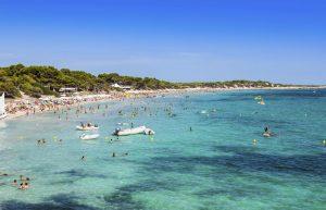 Motor Boat dinghies and holiday Makers Bathing in the Sea at Playa Den Bossa, Las Salinas Beach, Ibiza