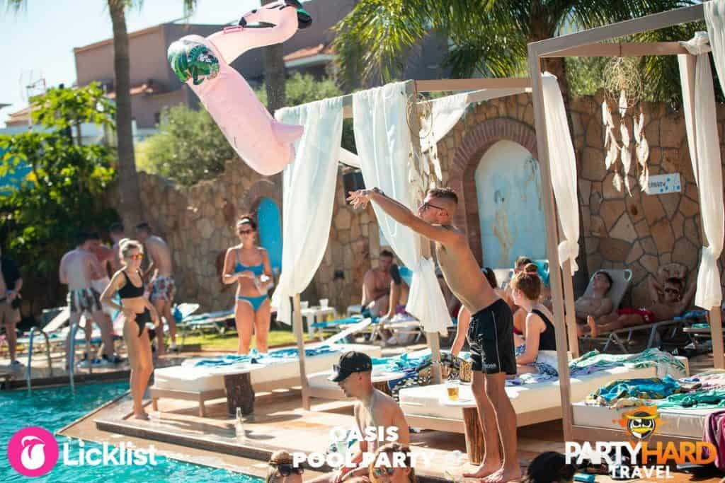 Lad Throwing an Inflatable Pink Flamingo Ring into the Malia Oasis Swimming Pool