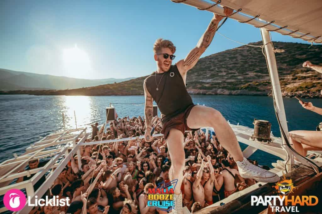 Booze Cruise DJ with Microphone Showboating in the Rigging, while sailing past the Malia Coastline