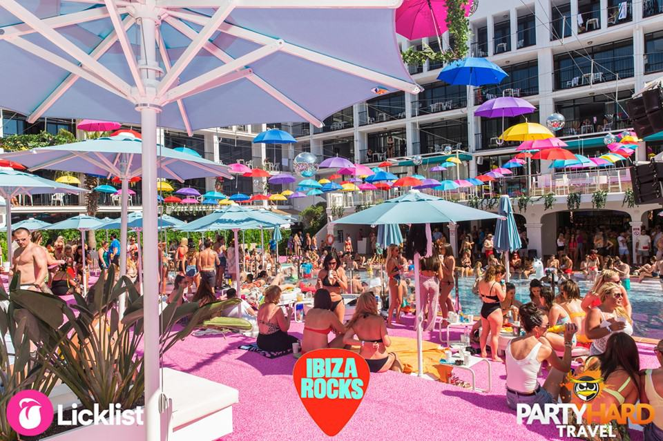 Lads and girls relax and chill out under the parasol sunshades by the Ibiza Rocks Pool