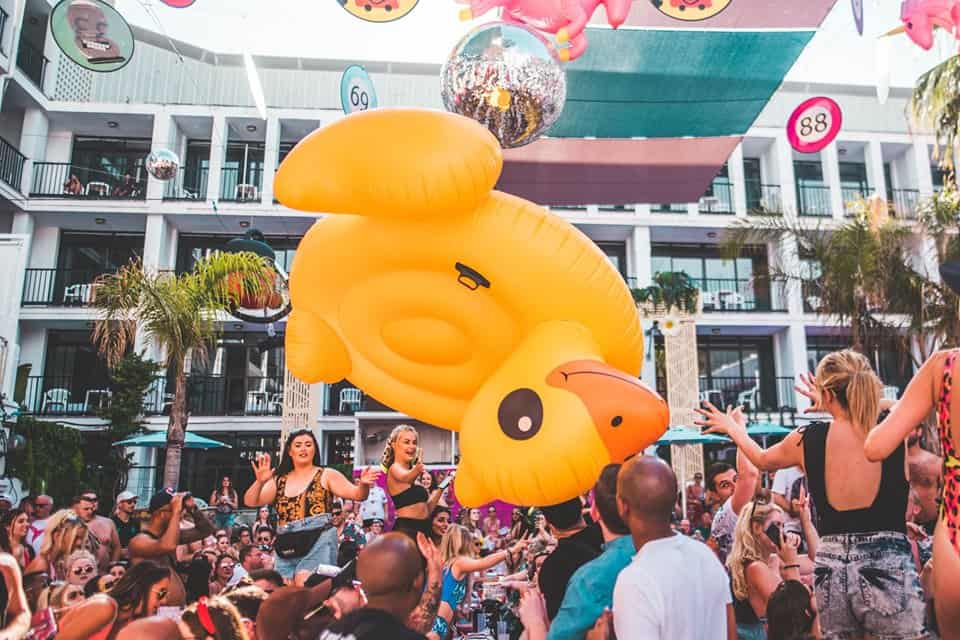 Revellers watch as a giant inflatable yellow and orange duck floats by at Ibiza Rocks Pool Event