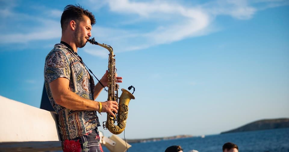 Saxophonist playing good vibes on the deck of the Ibiza Pukka Up Party Boat