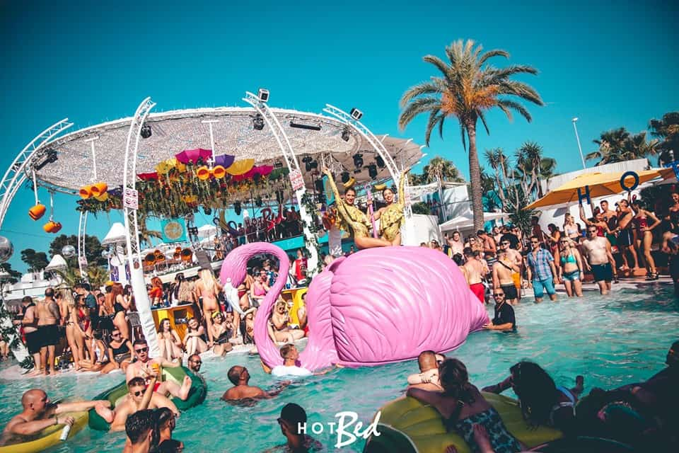 Two female performers sit on the back of a Giant pink flamingo floating in the O Beach club swimming pool