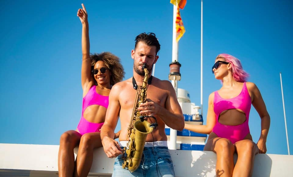 Saxophonist with backing dancers on board the Ibiza Pukka Up Boat Party