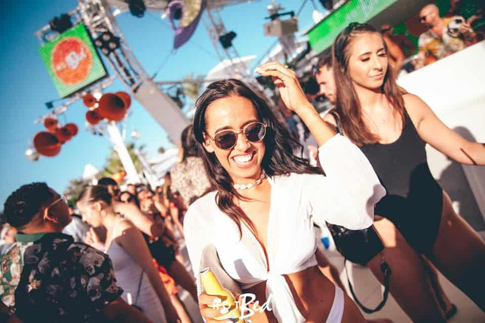 Girl with alcoholic drinks bottle enjoying the all round party atmosphere at Ibiza's O Beach Party