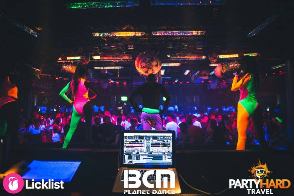 Dance Performers in Multicoloured costumes on stage in front of DJs at SuperClub Magaluf