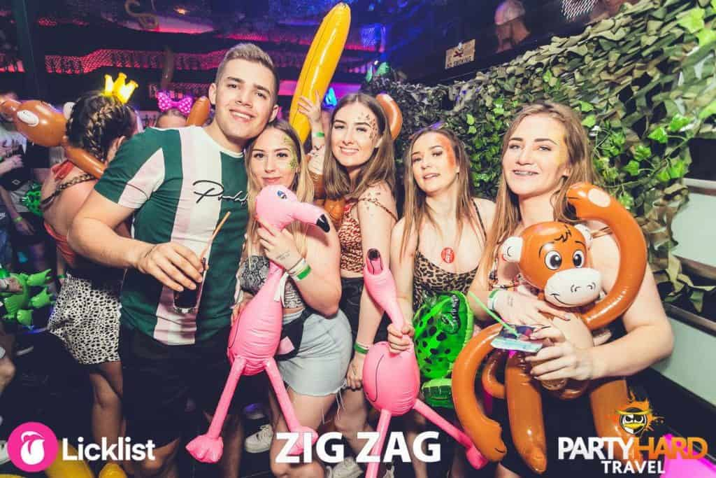 Pink Flamingos, Green Turtles and Orange Monkey Inflatables Posing with Clubbers in Malia