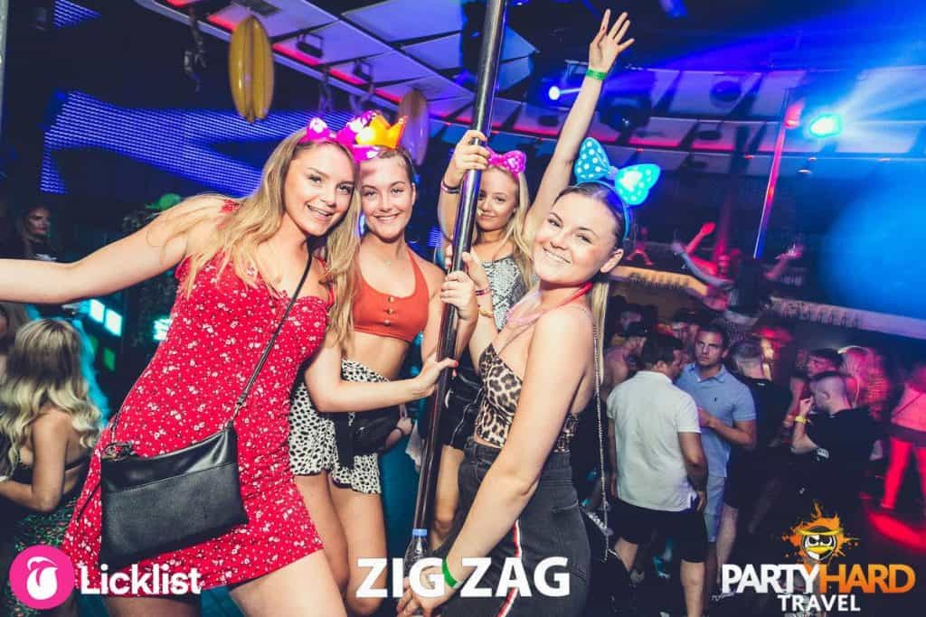 Group of girl clubbers posing by pole dancing pole at Malia Club