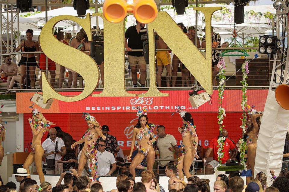 Five exotic female dancers performing on stage at O Beach hedonistic Sin Sunday party