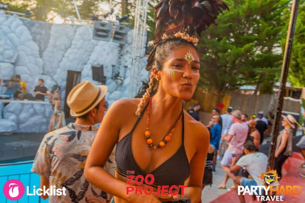 Girl showing off face paint and exotic headdress next to stage at Ibiza Zoo Festival