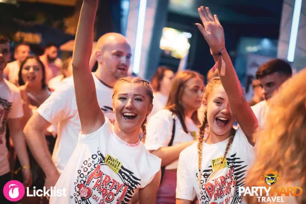 On the Ayia Napa Party Strip, Girls wearing Party Hard T-Shirts waving at friends