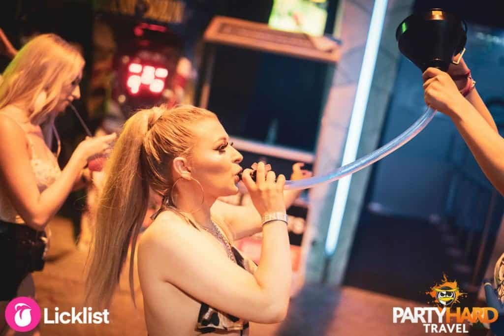Thirsty Girl taking an alcoholic drink from a funnel outside Ayia Napa Bar