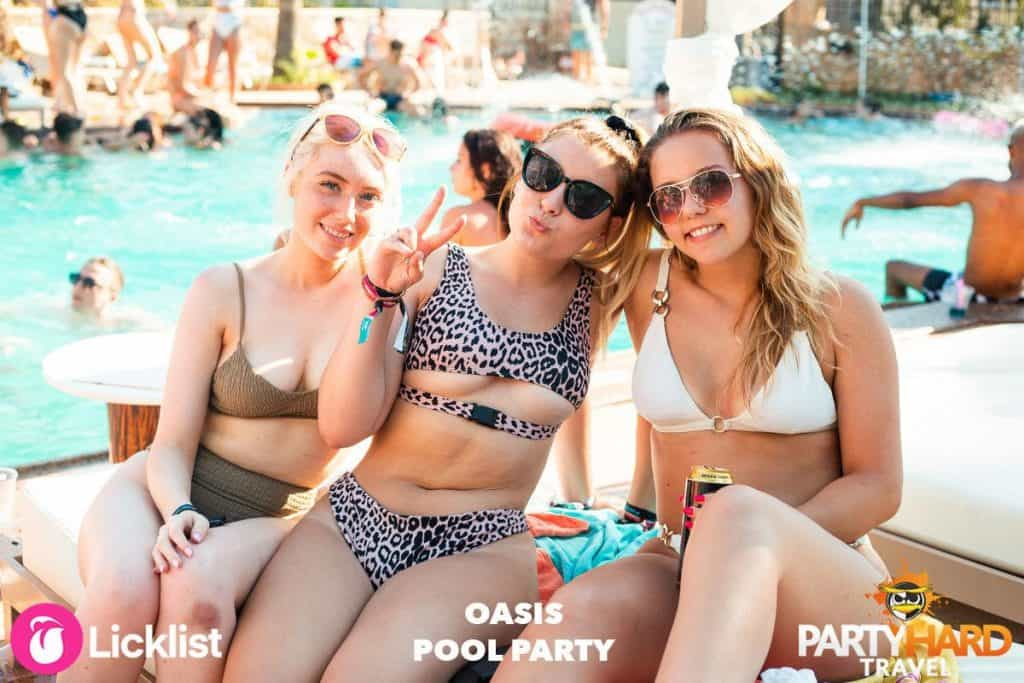 Three Girls sat on Sun Loungers Enjoying a Drink at the Oasis Pool Party in Malia