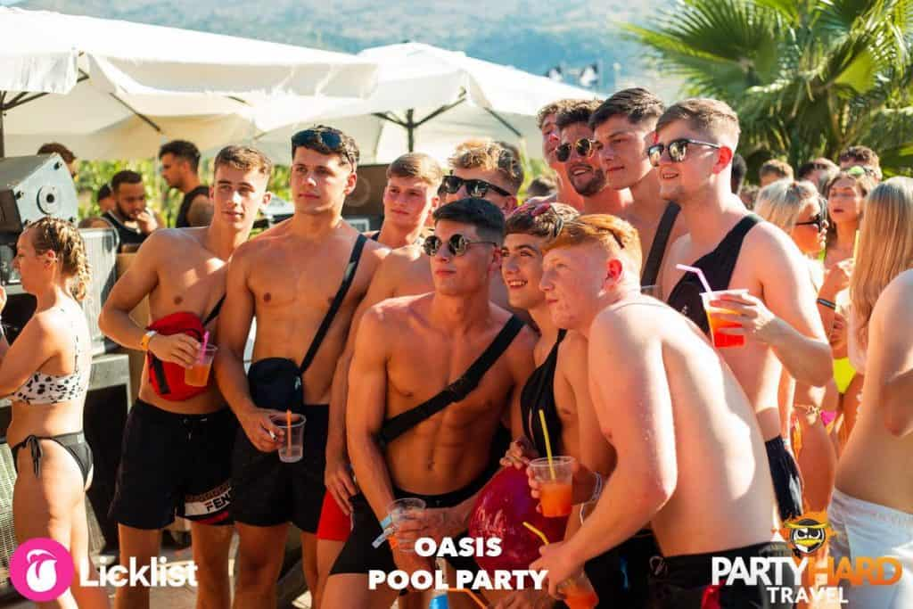 Group of Lads with Drinks Watching Something Interesting at the Pool Party in Malia