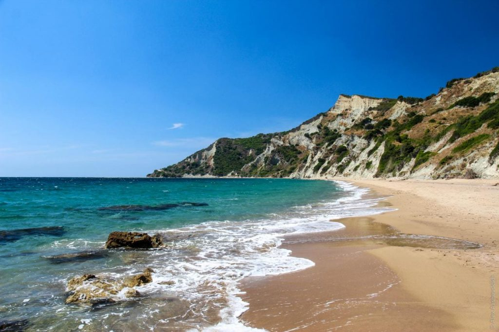 Rugged green mountains, golden sands and turquoise water of Arkoudilas Beach