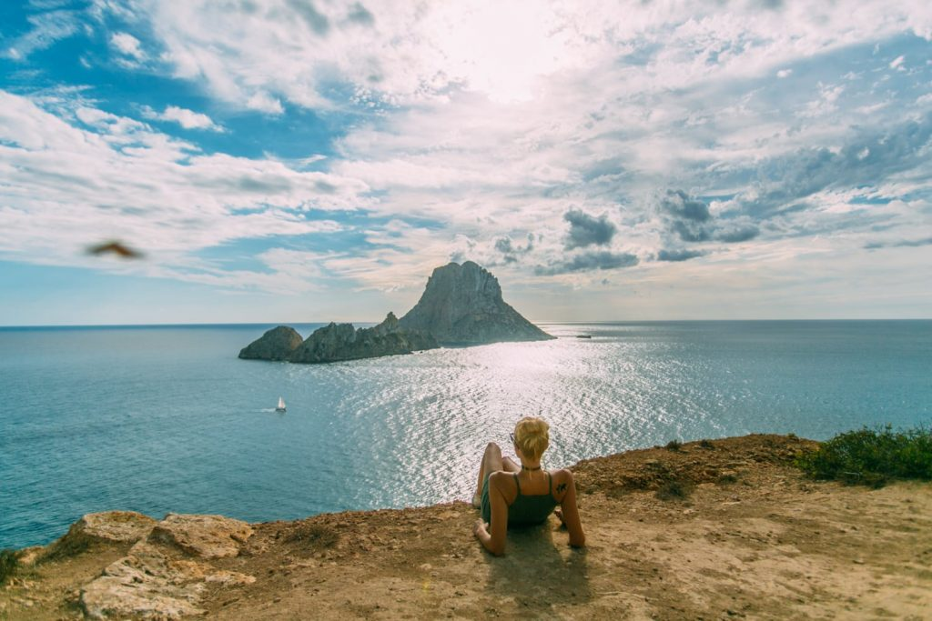 Girl lying on the beach looking out at the mythical island of Es Vedra