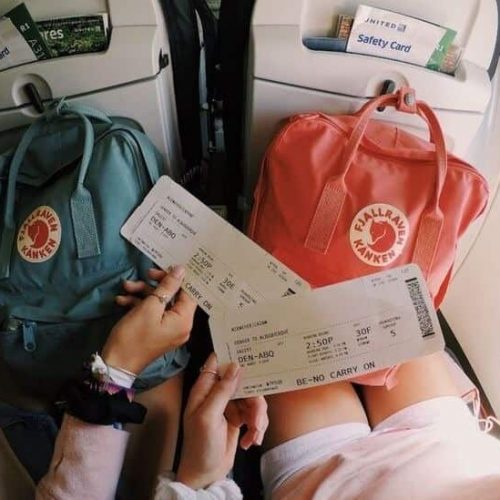 ultimate flight guide - two girls holding plane tickets on flights