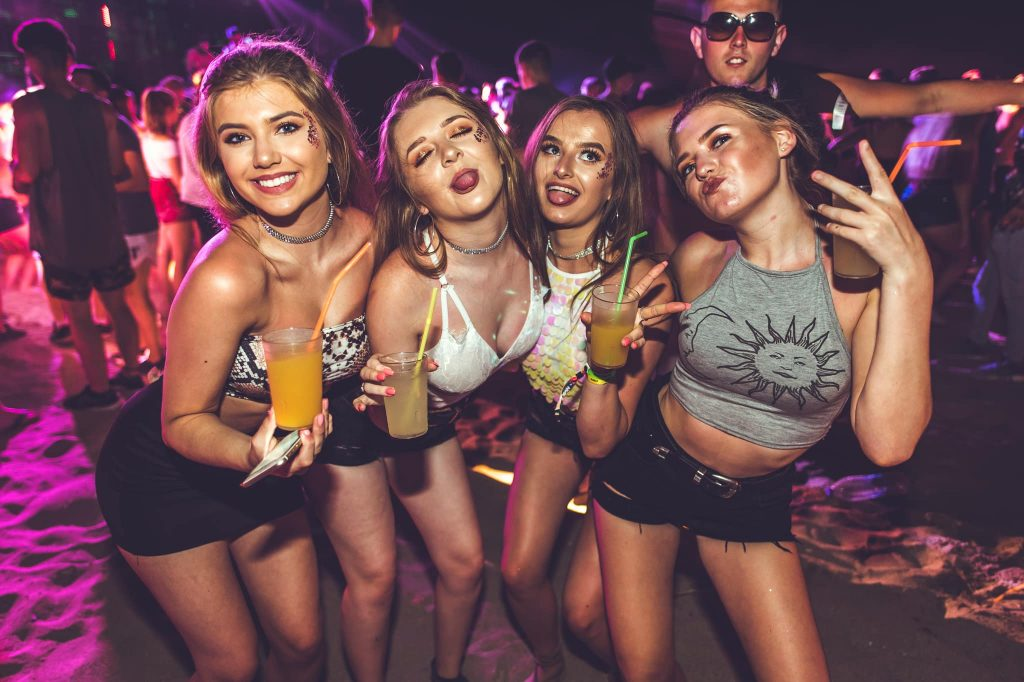 Four girls posing with drinks on the beach at the Full Moon Party event
