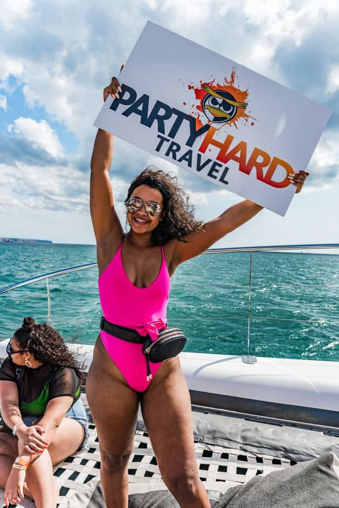 Party Hard holiding a Party Hard Travel sign
