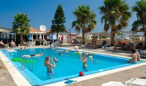 people relaxing and playing volleyball in malia hotel pool