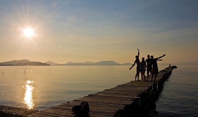 Group posing at sunset on Kavos's wooden deck jetty