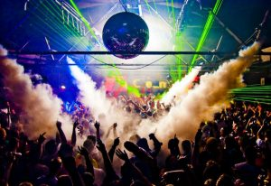 club in ayia napa smoke guns disco ball with people's hand up