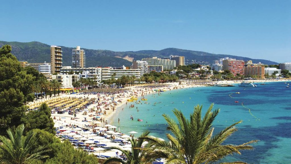 Palm trees surrounding Playa de Magaluf Beach packed with sun worshipers
