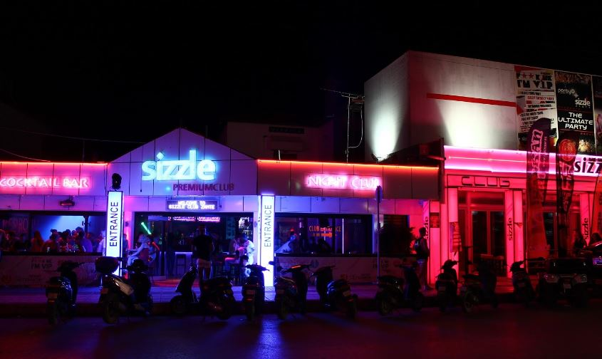 nightime neon lights on the front of sizzle club in zante